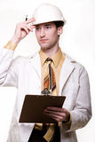 Male science engineer. Young attractive man wearing white lab coat tie and a white hard hat holding onto a clipboard Royalty Free Stock Photography
