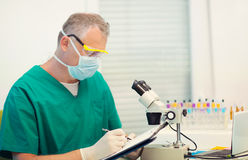 Male scientific researcher using microscope in the laboratory. Selective focus Royalty Free Stock Photo