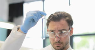 Male Scientist Analyzing Liquid In Test Tube Study Result Of Experiment In Modern Laboratory Over Group Of Researchers stock footage
