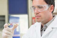 Male scientist analyzing pills in the laboratory. Close up side view of a male scientist analyzing pills in the laboratory Stock Photos