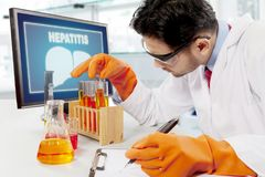Male scientist doing medical research. Picture of male scientist doing medical research for hepatitis disease. Shot in the hospital Stock Image