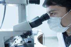 Male scientist doing microscope stock photography