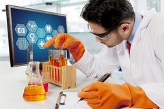 Male scientist doing chemical research. Male scientist doing science research in laboratory Royalty Free Stock Images