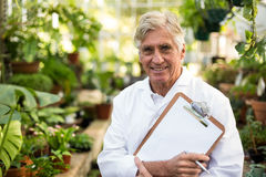 Male scientist holding clipboard at greenhouse. Portrait of male scientist holding clipboard while standing at greenhouse Stock Photography
