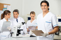 Male Scientist Holding Clipboard In Lab. Portrait of young male scientist holding clipboard with colleagues in background at laboratory Royalty Free Stock Photography