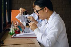 Male scientist inspect chemical liquid. Smart male scientist using magnifying glass to inspect blue chimical liquid in glass test tube. Chemist examine medical Stock Images
