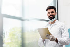 Male scientist in lab coat using digital tablet and smiling at camera. Bearded male scientist in lab coat using digital tablet and smiling at camera Stock Image
