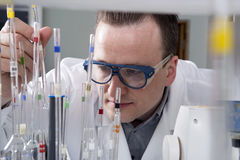 Male scientist with laboratory pipettes Stock Image