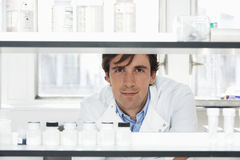 Male Scientist Looking Through Shelves. Portrait of confident male scientist looking through shelves in laboratory Stock Image