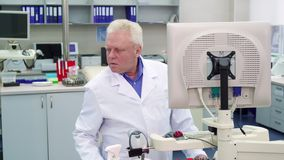 Male scientist looks to the side at the laboratory. Aged male scientist looking to the side at the laboratory. Senior lab worker putting his hand on keyboard royalty free stock photos