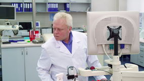 Male scientist looks to the side at the laboratory. Aged male scientist looking to the side at the laboratory. Senior lab worker putting his hand on keyboard stock video footage