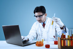 Male scientist making biotechnology. Experiment with chemical fluid in laboratory Royalty Free Stock Photography