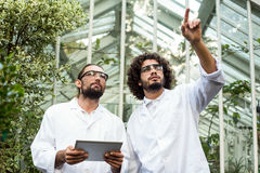 Male scientist pointing while colleague holding digital tablet Stock Photo