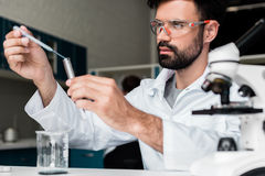 Male scientist in protective glasses making experiment in chemical lab Royalty Free Stock Image