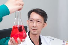 Male scientist standing with techer in lab worker making medical. Research in modern laboratory. Scientist holding documents folder with analysis results Stock Photography