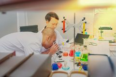 Male scientist standing with techer in lab. Worker making medical research in modern laboratory. Scientist holding documents folder with analysis results Stock Images