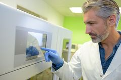 Male scientist takes off data from facilities in laboratory. Male Stock Photo