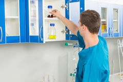 Male scientist in uniform is looking at bottle with chemical su. Male scientist in uniform is Stock Photography