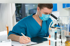 Male scientist in uniform is looking through a microscope and go. Ing to write down notes of his research in a laboratory. Healthcare and biotechnology concept Stock Photography