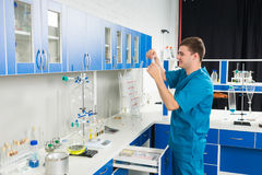 Male scientist in uniform is looking at sachet with chemical su. Male scientist in uniform is Royalty Free Stock Photography