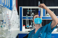 Male scientist in uniform wearing a mask is holding a big test t. Ube with blue liquid, making some research in a laboratory. Healthcare and biotechnology Royalty Free Stock Images