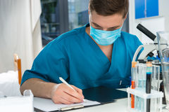 Male scientist in uniform is writing down notes of his research. After looking through a microscope in a laboratory. Healthcare and biotechnology concept Stock Photography