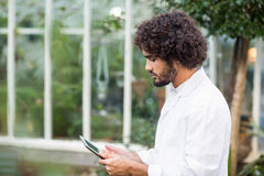 Male scientist using digital tablet. Side view of male scientist using digital tablet outside greenhouse Royalty Free Stock Images