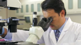 Male Scientist Using Microscope In Laboratory stock video footage