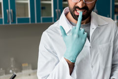 Male scientist in white coat removing protective glove by teeth in lab. Bearded male scientist in white coat removing protective glove by teeth in lab Stock Photography