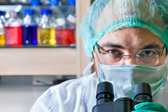 Male scientist working in a laboratory. Wearing glasses, a surgical cap and mask looking up over the ocular of his microscope at the camera, close up of his Royalty Free Stock Photo