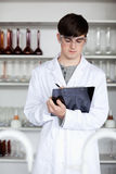 A male scientist writing on a clipboard. Portrait of a male scientist writing on a clipboard in a laboratory Stock Images
