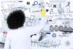 Male scientist writing research formulas. Young scientist is writing research formulas with marker on interface screen in the laboratory Stock Photo