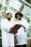 Male scientists discussing over clipboard. Low angle view of male scientists discussing over clipboard outside greenhouse Royalty Free Stock Photography