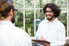 Male scientists smiling while discussing. Outside greenhouse Stock Photography