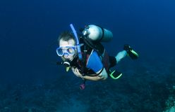 Male scuba diver. Scuba diver swims on reef blowing bubbles Royalty Free Stock Photography