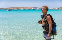 Male scuba diver standing on a beach. Male scuba diver with equipment standing on a beach with turquoise waters Royalty Free Stock Photo