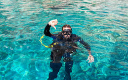 "Male scuba diver gives ""dive down"" sign. Male scuba diver gives ""dive down"" sign in mediterranean sea Royalty Free Stock Images"