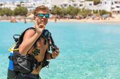 Male scuba diver gives the OK sign. In front of turquoise waters Royalty Free Stock Photo