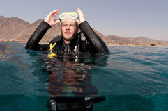 Male scuba diver on surface. Scuba diver places mask on head before dive with mountain in the background Stock Images