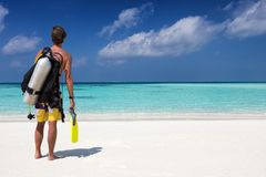Male scuba diver on a tropical beach. Male scuba diver with diving gear on a tropical beach Royalty Free Stock Images