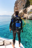 Male scuba diver watches the scene from the diving boat. Male scuba diver looks at the mediterranean sea from the diving boat Royalty Free Stock Photos