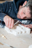 Male Sculptor Carving a Plaster Model. A caucasian male in paint-splattered hoodie using a precision knife and sculpting a white plaster model on a desk Stock Photo