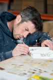 Male Sculptor Trimming a Plaster Model with Precision Knife. A caucasian male in paint-splattered hoodie using a precision knife and trimming a section of a Stock Photos