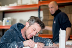 Male Sculptor with Utility Knife Trimming a Sculpture. A caucasian men in paint-splattered hoodie utilizing a precision knife to trim a plaster model while a Royalty Free Stock Photos