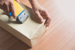 Male sealing with tape small box for moving. Close up of a hands stock photography