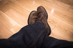 Male seat and legs in shoes on the wooden floor. Closeup male seat and legs in shoes on the wooden floor Royalty Free Stock Images