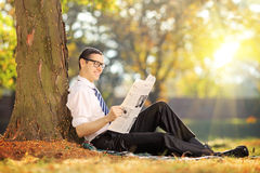 Male seated on grass reading a newspaper in a park. Young man with tie seated on a grass reading a newspaper in a park on a sunny day Royalty Free Stock Image