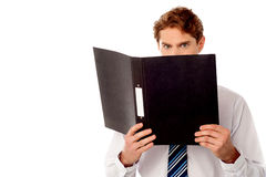 Male secretary in anger reviewing file. Angry manager reviewing company documents Stock Image