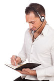 Male secretary or personal assistant. Wearing a headset making an appointment in a handheld diary for his boss, studio portrait isolated on white with copyspace Stock Photos