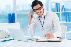 Male secretary. Portrait of a male office worker receiving a call Royalty Free Stock Image